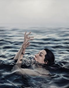 A woman sinks and emerges at the surface of a foggy sea.